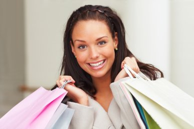 Closeup portrait of happy young female carrying shopping bags