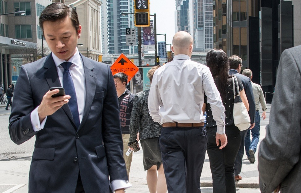 Banker looking at his phone on the street